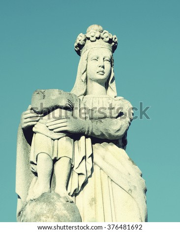 Old stone statue of the Virgin on tomb and Jesus Christ with rolled his head to the cemetery in Ukraine in vintage style - stock photo
