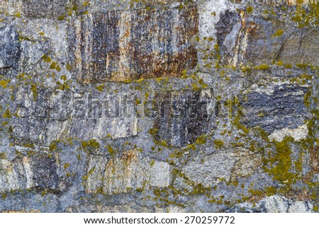 Old stone wall background covered with moss - stock photo