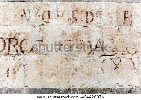 old stone wall with ancient lettering at a historic building in Florence, Italy - stock photo
