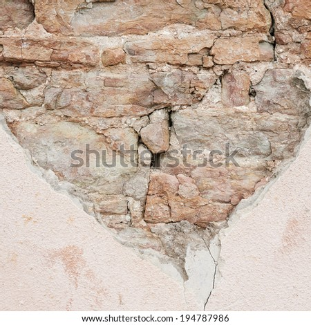 Old stone wall with lime layer falling off fragment as a background grunge texture - stock photo
