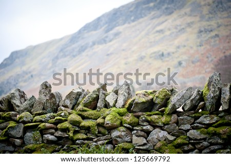 Old stone wall with moss - stock photo