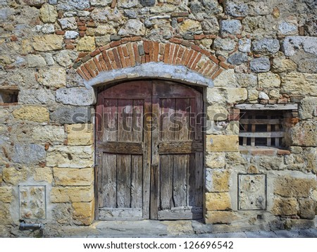 Old stonewall with closed wooden door and window