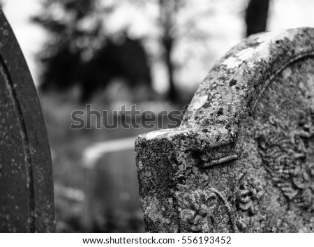 Old stonework graves and tombstones seen in a village cemetery.