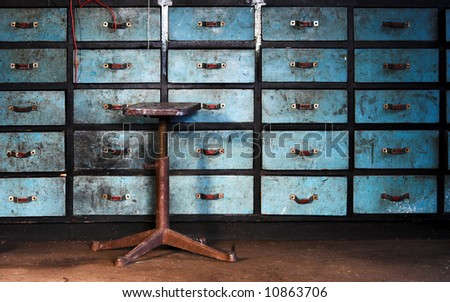 Old stool on drawers background - stock photo