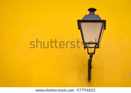 Old street lamp on a yellow wall background - stock photo