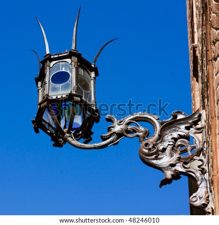 old street lamp with dragon shaped bracket on the wall of antique italian building  - stock photo