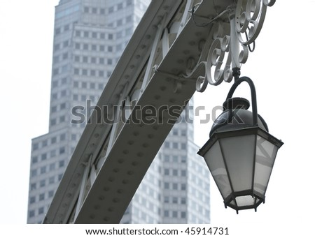 Old street light against a modern building isolated on white