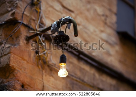 Old street light bulb on the wall of an old building