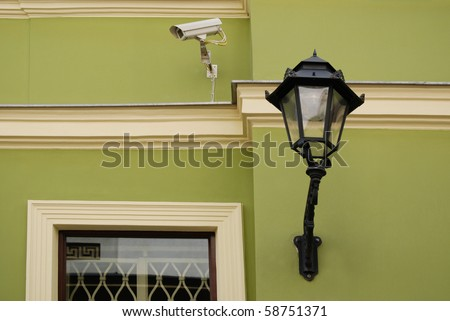 Old street light on a green wall. - stock photo