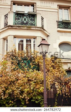 old streetlight near grey house - stock photo