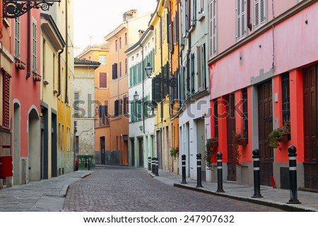 Old streets in Italian town with houses painted in different colors, Parma, Italy - stock photo