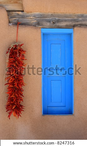 Old stucco building in Taos New Mexico with a colorful window and some ristras hanging next to it. - stock photo