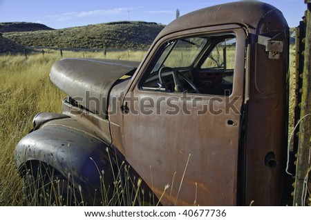 Old studebaker truck rusting in the farm field.It has the morning sun on it. - stock photo