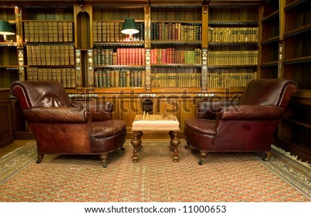 Old studying room with two leather armchairs and chess game - stock photo