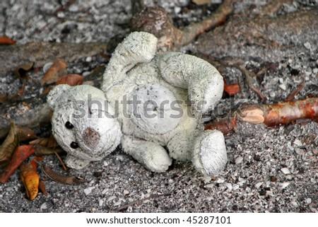 old stuffed teddy bear laying on ground - stock photo