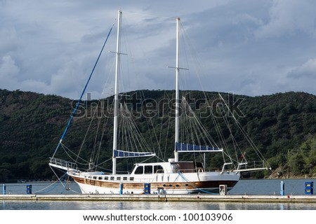 Old style big two mast sailing vessel moored. Mountain background. - stock photo