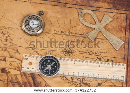 Old style brass pocket watch and cross on antique map - stock photo
