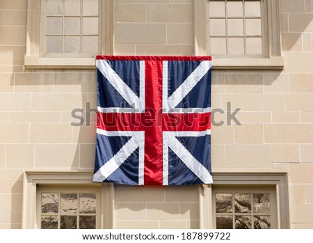 Old style English Flag hung outside historic Carlyle House in center of old town of Alexandria in Virginia USA - stock photo