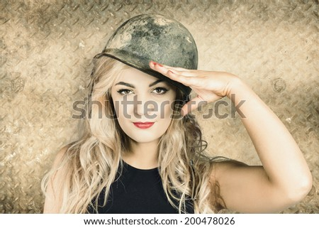 Old style portrait of an enthusiastic blond army pin-up girl wearing grunge helmet saluting for enrolment at a new recruit office. Sign up draft - stock photo
