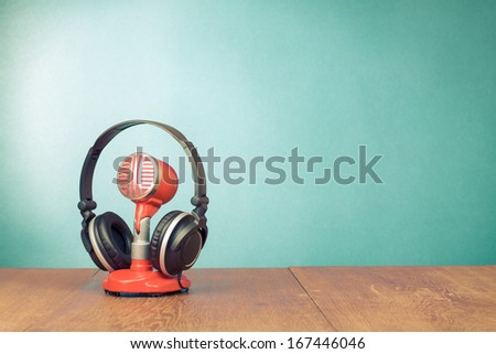 Old style red microphone, headphones for retro background - stock photo