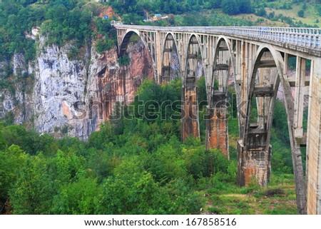 Old style stone bridge across deep canyon - stock photo