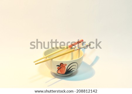 Old style thai ceramic bowl with wooden chopsticks. - stock photo
