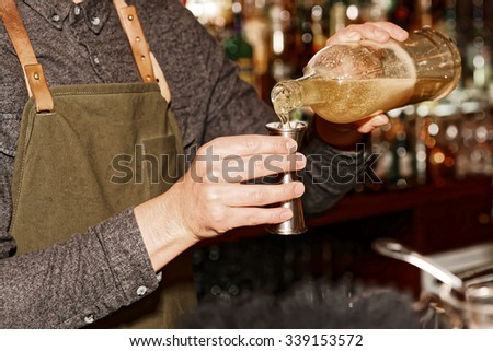 Old styled bartender is pouring liquor in metal jigger - stock photo