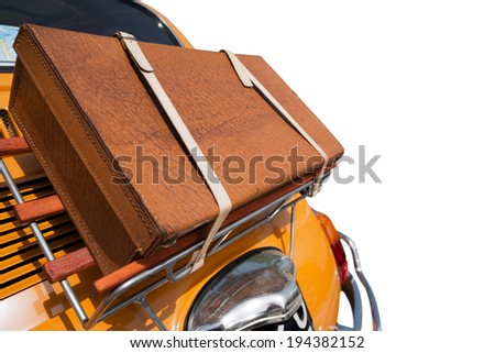 Old Suitcase on the back of a Little Car / Old leather suitcase tied on the back of a small orange car isolated on white background  - stock photo