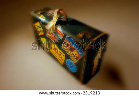 Old Suitcase on warm background with lots of travel stickers - stock photo
