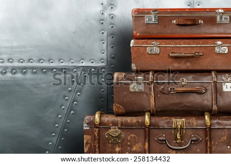 Old suitcases against metal wall background or texture with copyspace - stock photo
