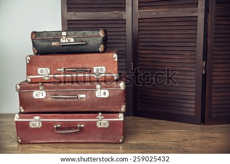 Old suitcases on a background of dark wood screen - stock photo