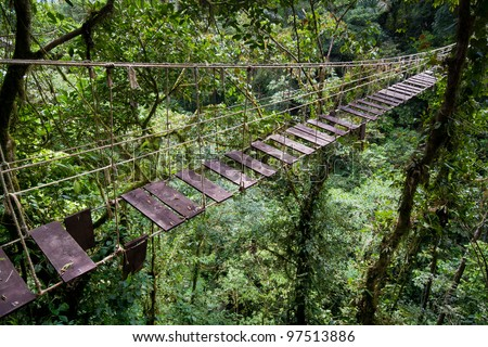 Old suspension bridge in rainforest of Costa Rica - stock photo