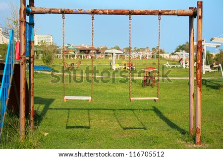 Old swing on the playground - stock photo