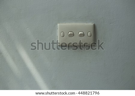 Old switches on grey wall and light rays.