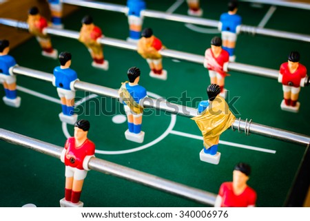 old table soccer with red and blue players fixed with adhesive tape, selective focus.