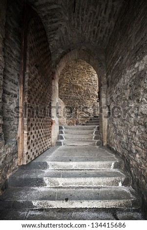 Old Tallinn street fragment with arch wooden door and stone walls - stock photo