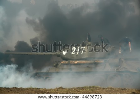 Old tank in grey smoke on the battlefield. - stock photo