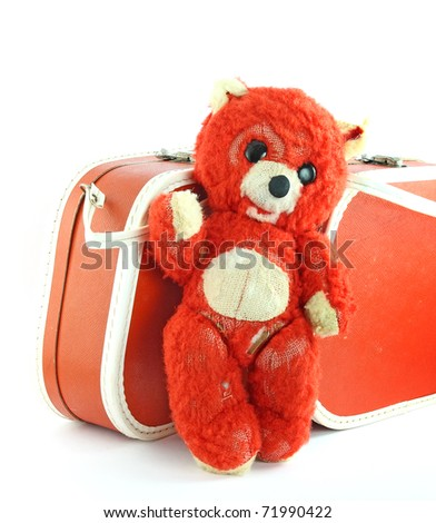 Old teddy bear and suitcase - stock photo