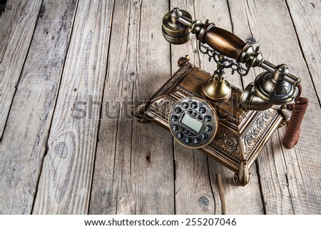 Old telephone on wooden background. Copy space on the bottom. - stock photo