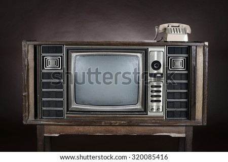 Old  telephone put on an vintage television on brown background. - stock photo