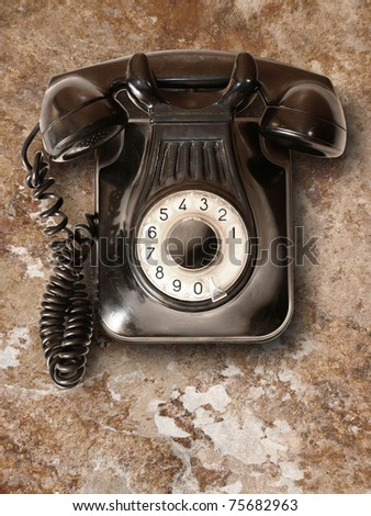 Old telephone with rotary dial on wall - stock photo