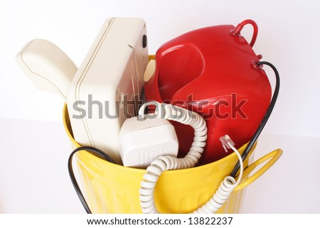 Old telephones in the yellow dustbin isolated - stock photo