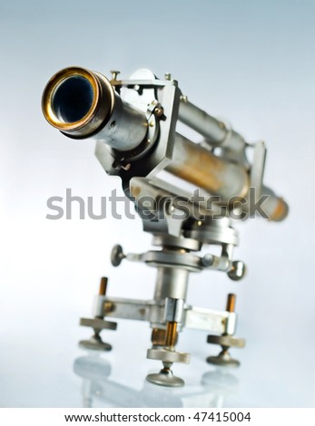 Old telescope with reflection, blue background - stock photo