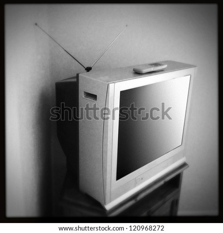 Old television and remote control - stock photo