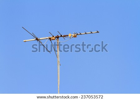 Old television antenna on blue sky background - stock photo