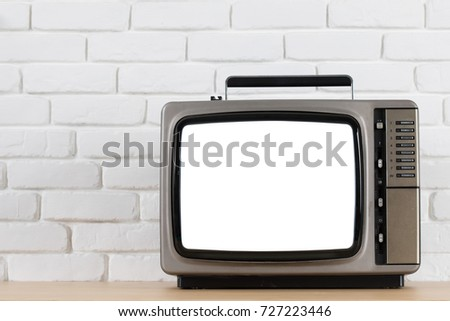 Old television with cut out screen on a white brick wall background.