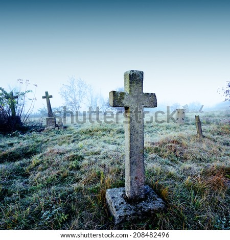 Old terrible stone cross on cemetery on background of sky - stock photo
