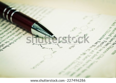 old textbook with pen - stock photo