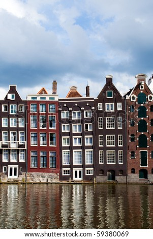 Old 17th and 18th century brick houses along a canal in Amsterdam, Holland. - stock photo