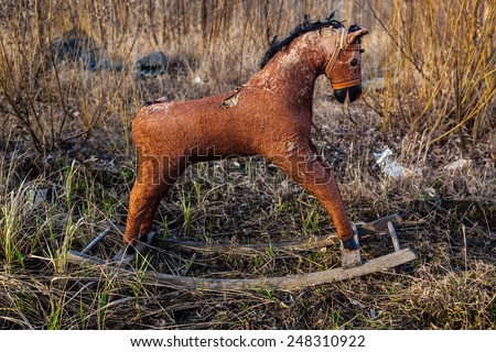 Old threadbare rocking horse thrown away to the dump in the field - stock photo